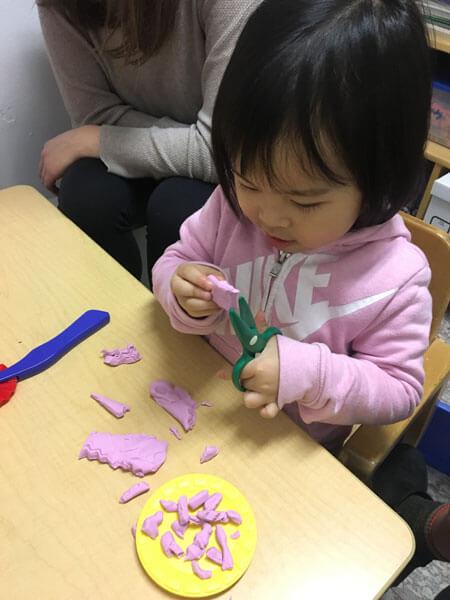 Child cutting clay